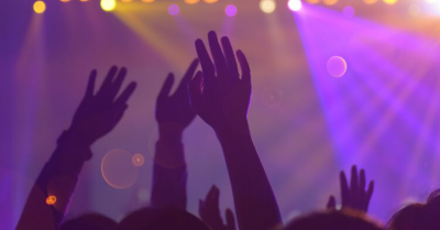 fans raising their hands in the air at a concert